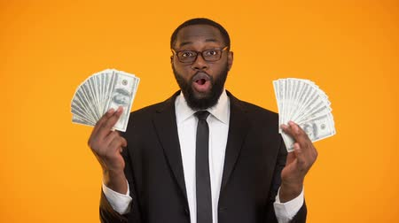 lucrative : Black male in eyeglasses showing bunches of cash, profit, lucrative business