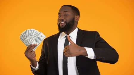 charisma : Satisfied black businessman showing dollar cash and thumbs-up gesture, income