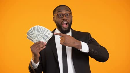 lucrative : Cheerful afro-american man in formalwear pointing at bunch of dollar cash, coach
