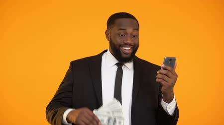 lucrative : African-american male in business suit holding phone and dollar bills, cashback