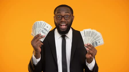 rentável : Smiling african-american businessman showing bunches of dollar cash, profit