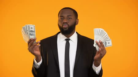 rentável : Sexy african-american male in suit playing with dollar banknotes and making kiss Vídeos
