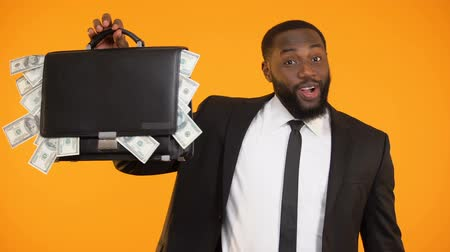 харизматический : Joyful african-american businessman showing handbag with dollar cash, income