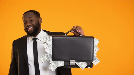 rentável : Funny black businessman holding handbag with dollar cash and showing thumbs-up Vídeos