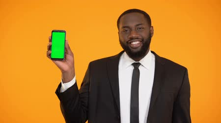 charisma : Smiling afro-american man in formalwear showing prekeyed phone, advertisement