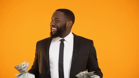 lucrative : Afro-american male in formal suit making dancing movements with dollar cash Stock Footage