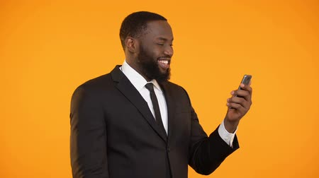 харизматический : Successful afro-american businessman reading news on phone, making yes gesture