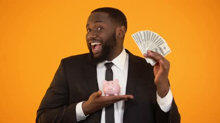 kumbara : Cheerful african-american man holding piggybank and showing dollar cash, deposit Stok Video