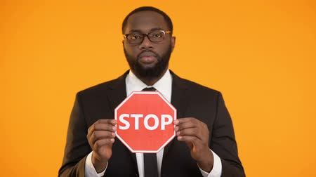 evasion : African-american male showing stop sign, antiracism campaign, social equality