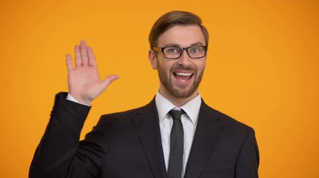 partneři : Friendly man in suit waving hand, saying hello, inviting for work, education