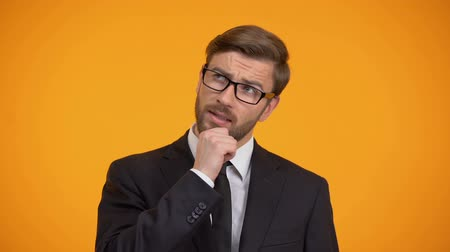 concern : Pensive male thinking about business ideas for start up, orange background Stock Footage
