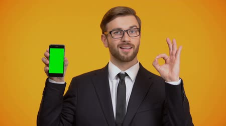 başkan : Man of business showing smartphone with green screen and ok gesture, cash-back
