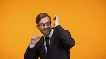rentável : Funny businessman dancing, isolated on orange background, successful contract