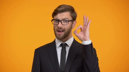 verimlilik : Handsome businessman showing ok sign and winking, isolated on orange background
