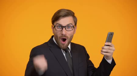 igen : Man looking at smartphone and doing yes sign, favorable credit term, betting