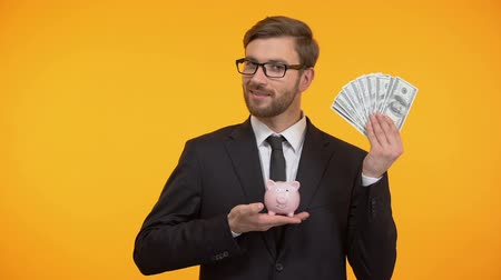 mevduat : Male in suit showing piggy-bank and dollars, pension fund, retirement income