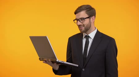 businesspeople : Happy man holding laptop showing thumbs up, satisfied with new software work Stock Footage