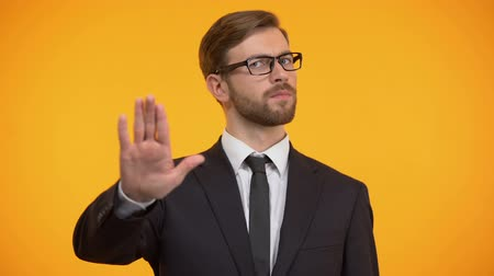 barriers : Business person doing stop gesture, rejecting to overwork, orange background