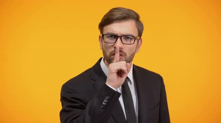 művelt : Serious male showing silence gesture, nondisclosure of personal data, secret