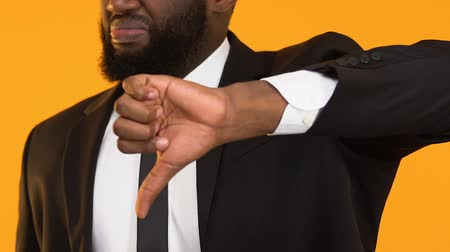 insecure : Afro-American man in suit showing thumbs down, failed new business project