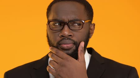 мысль : Black business man in glasses touching beard, looking for best option, decision