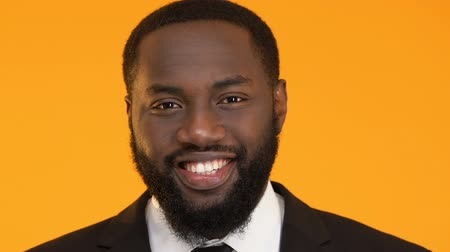 bankier : Successful Afro-American male smiling into camera isolated on yellow background