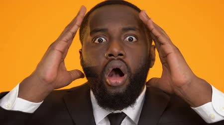 удивительный : Shocked black man in suit holding head, bad financial situation, bankruptcy