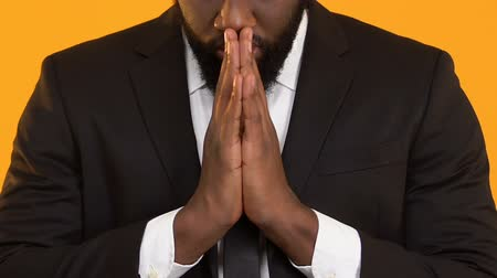 pleading : Superstitious black male praying before important deal, hoping for success