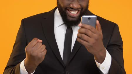 gesztus : Happy Afro-American male in suit holding smartphone showing yes gesture, lottery