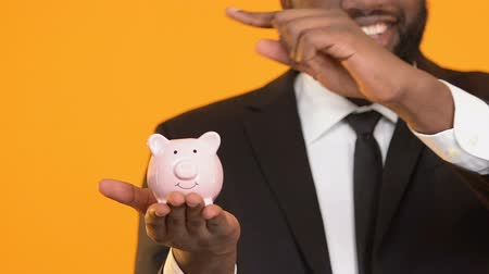 save the animals : Smiling black man in suit putting coins in piggy bank capital investment savings