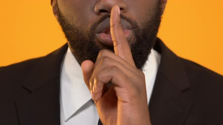 forefinger : Black man in suit showing silence sign, illegal tax evasion, corporate secret