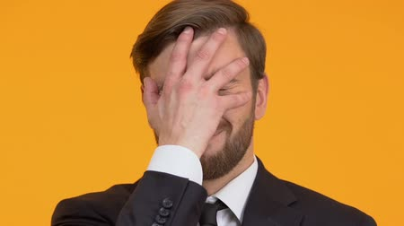 смущенный : Embarrassed man making facepalm, shocked with his mistake, loser, close-up