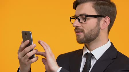 atualizar : Happy man scrolling smartphone, client satisfied with network and tariff quality Stock Footage