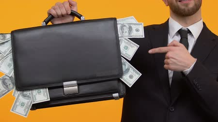 bribe : Man pointing at money sticking out from his case, additional income, capital