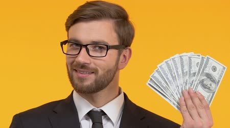 depósito : Smiling man holding cash in hand, perks and bonuses, isolated bright background Stock Footage