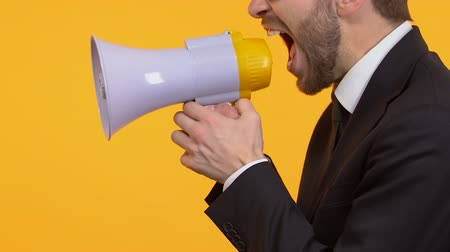 gritante : Irritated man shouting in megaphone, protest campaign, election, side-view