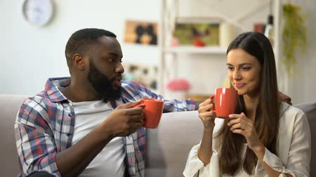 mluvení : Nice mixed-race couple talking at home, drinking tea after work day, relations