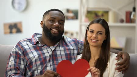 two hearts : Hugging mixed-race couple showing paper heart to camera, sitting on sofa at home