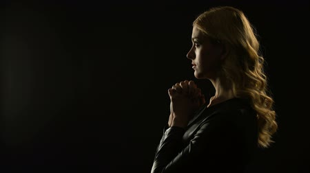 acreditar : Blond woman praying in dark place, asking for forgiveness, sinner confession