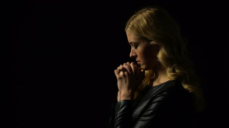 miserável : Miserable lady praying in darkness under heaven light, sinner confession, faith