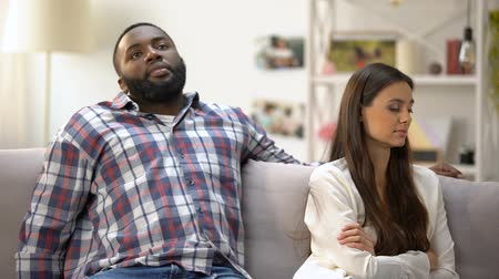 přestupek : Afro-American male reconciling with offended girlfriend, sitting on sofa at home