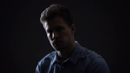 temper : Young man looking at camera isolated on black background, personality dark side Stock Footage
