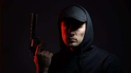 villain : Male hooligan with gun against dark background, danger criminal ready to robbery Stock Footage