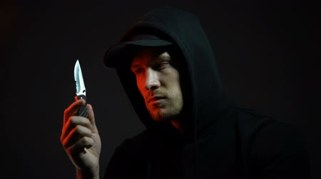 villain : Confused young man holding knife, regretting about made crime, dark background Stock Footage