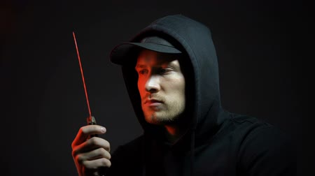 villain : Pensive man in hoodie holding knife, thinking about doing crime, melee weapon
