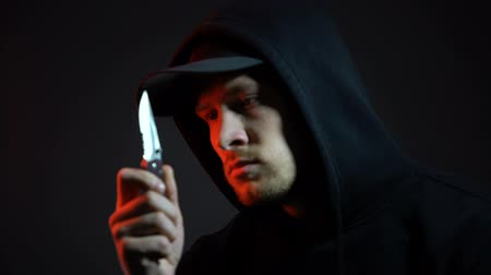 villain : Angry man in hoodie holding knife on place of crime, trying to hide evidence