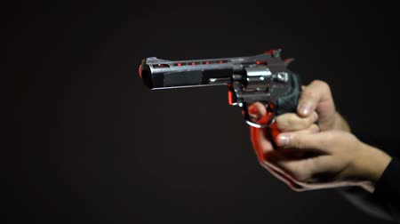 villain : Dangerous contract killer aiming gun isolated on black background, crime