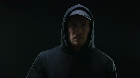 villain : Confident male gangster in hoodie looking at camera against black background