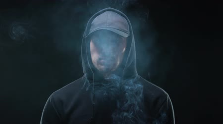 cinayet : Male bully in hoodie smoking cigarette against dark background, night criminal Stok Video