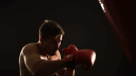 self injury : Male boxer punching boxing bag, warming up before competition, martial arts Stock Footage